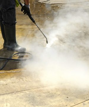 Worker cleaning with pressurized water the pavement of city streets